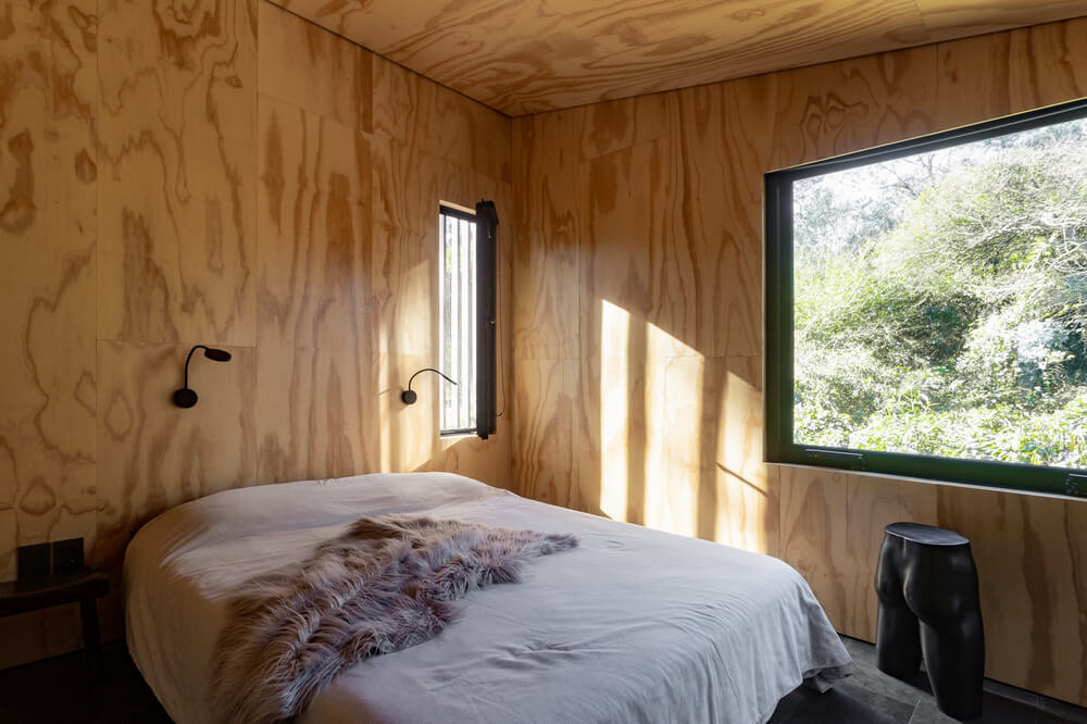 This is the bedroom that has a platform bed topped with wall-mounted lamps that stand out against the wooden walls and ceiling.