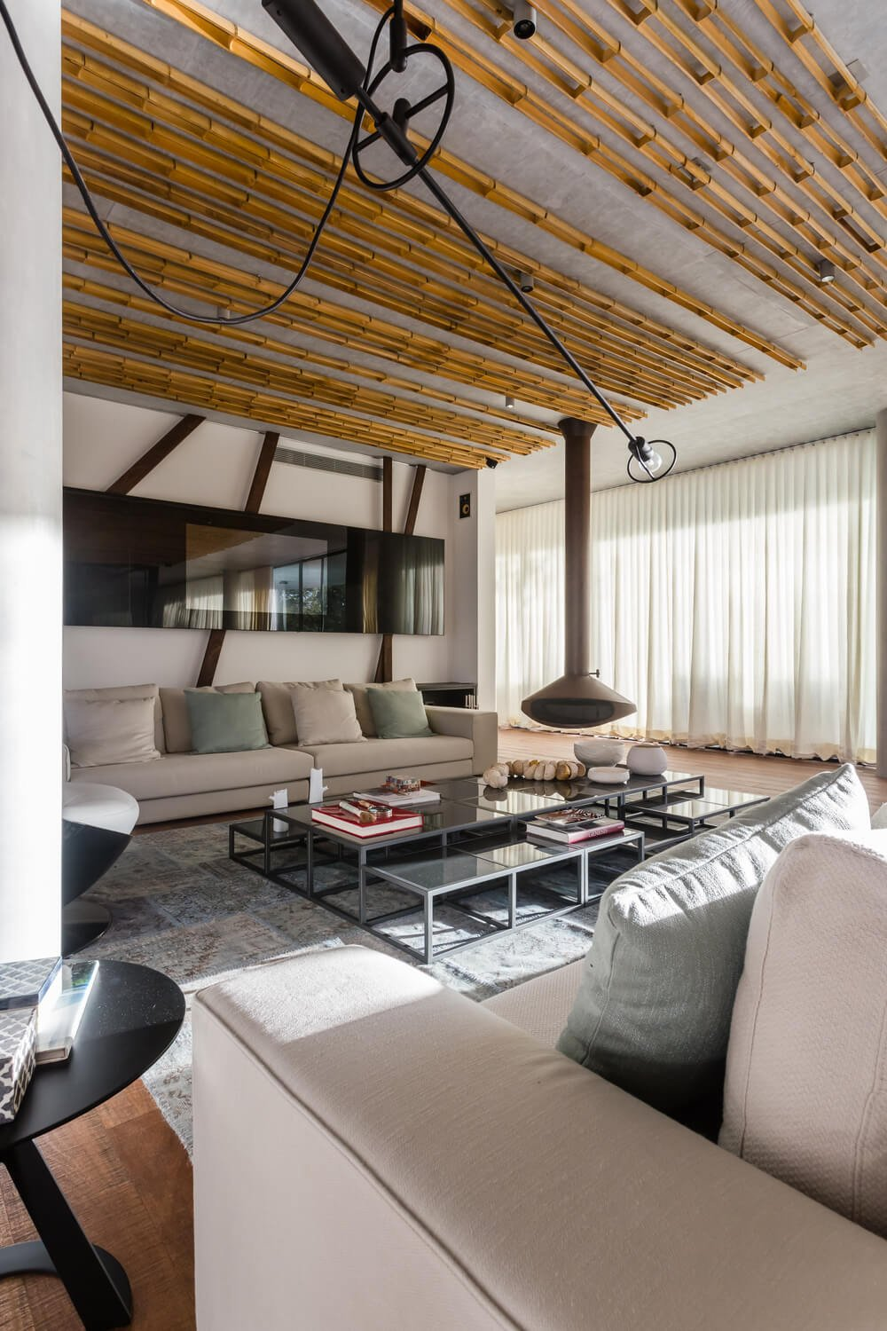 This is a full view of the metal and glass coffee table in the middle of two sectional sofas and has a view of the TV and the modern hanging fireplace on the far corner.