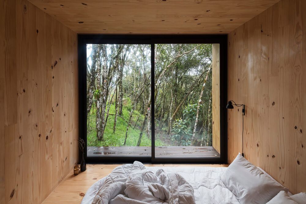 On the far side from the bed is the glas wall that brings in natural lighting.