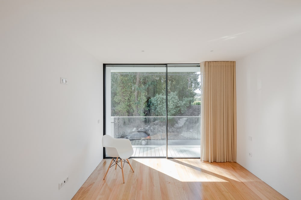 This corner of the house has a glass door that leads to the balcony that has glass railings.
