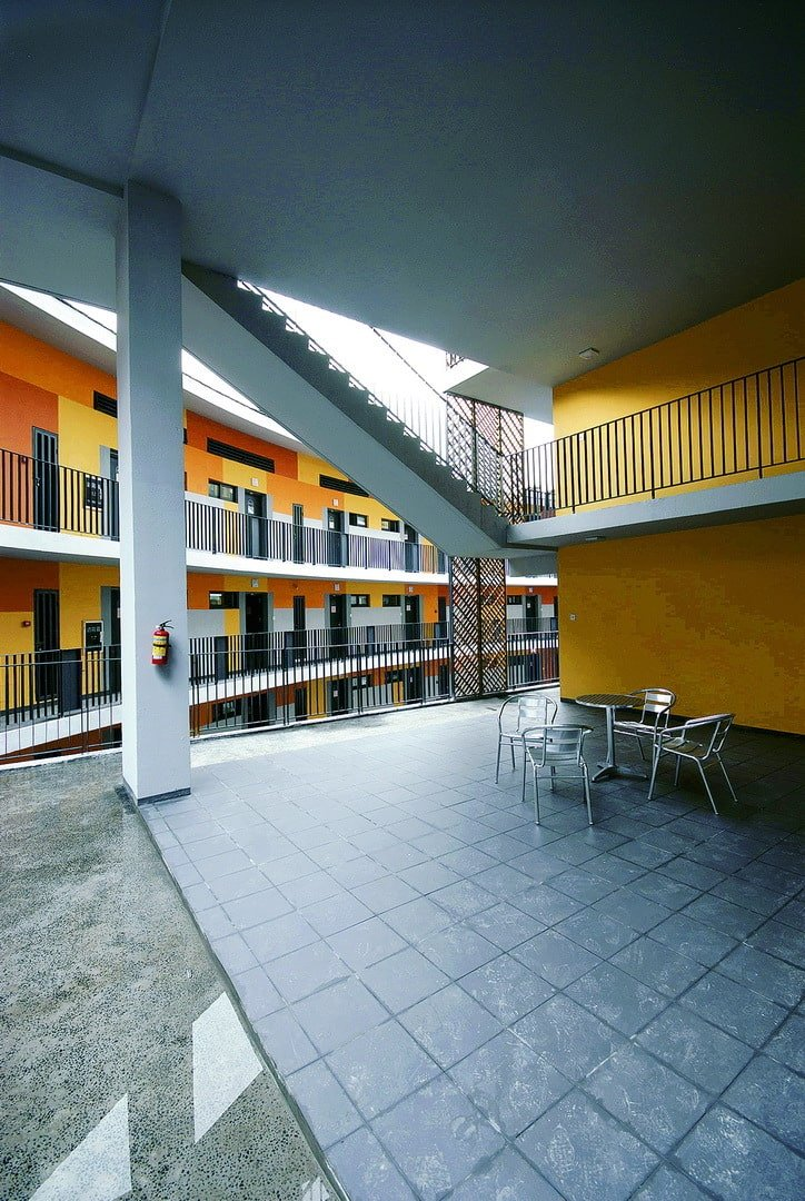 This is another outdoor area of the collective housing with yellow tones on its exterior walls complemented by white accents and wrought iron railings.