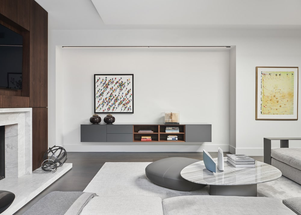 The sofa is paired with a white marble coffee table and a gray ottoman.