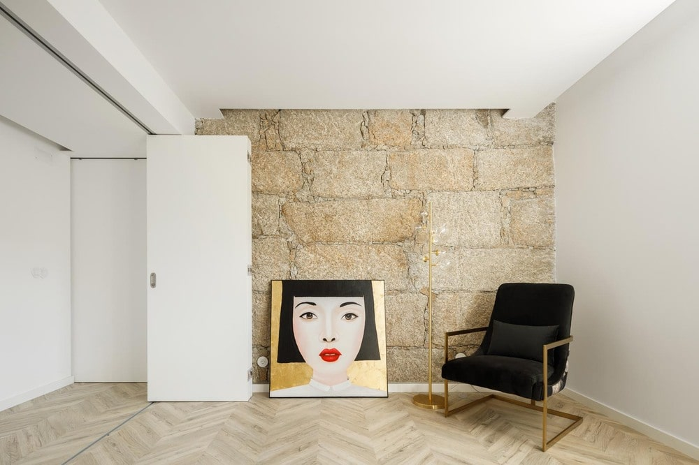This is a corner of the house with a large textured stone wall that complements the chair and the colorful artwork.