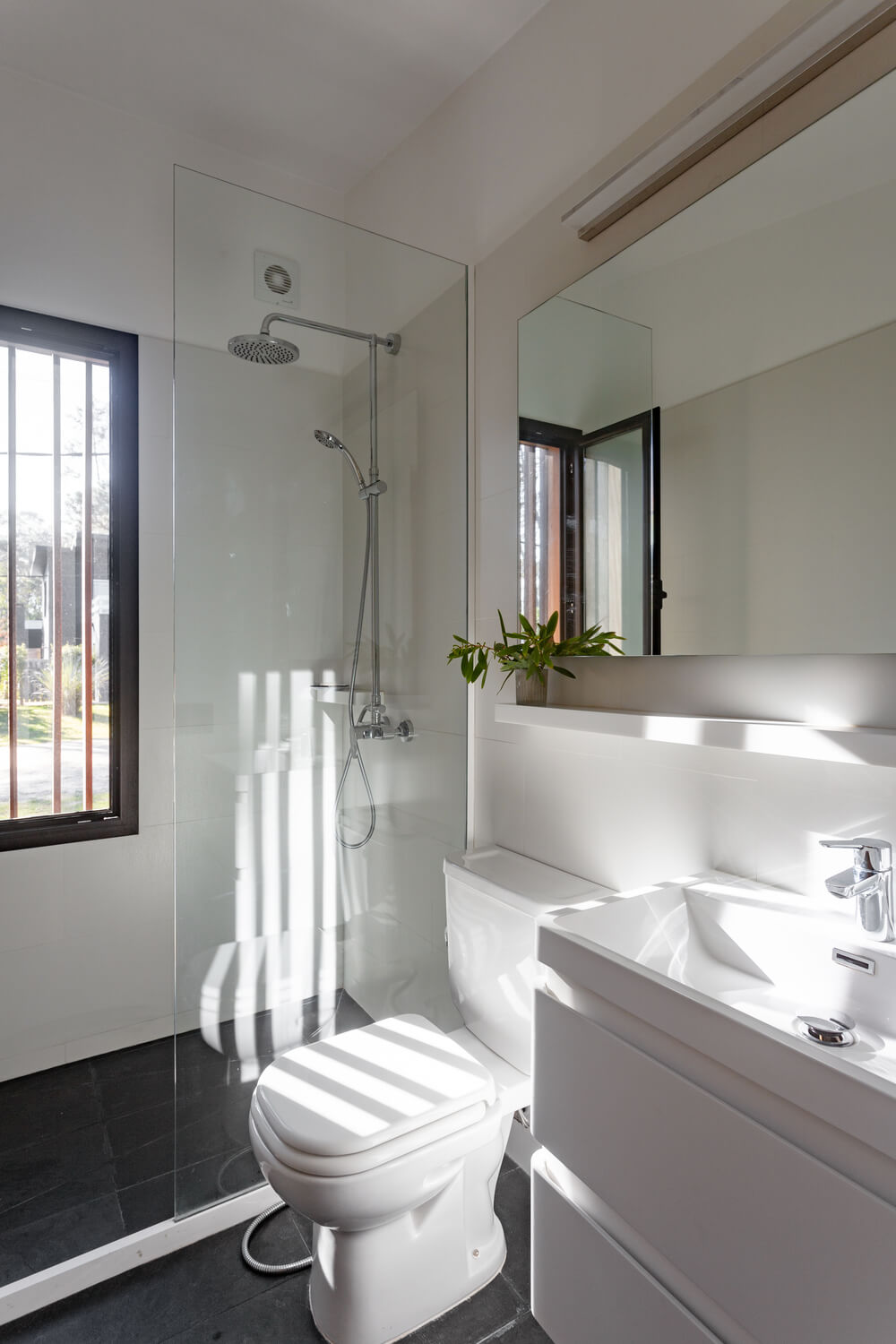 The bathroom has a consistent bright white tone to its shower area, vanity and toilet brightened by the natural light.