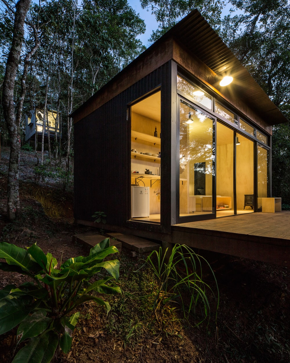 The glas walls and doors of the house glow warmly from the interior lights that escape.