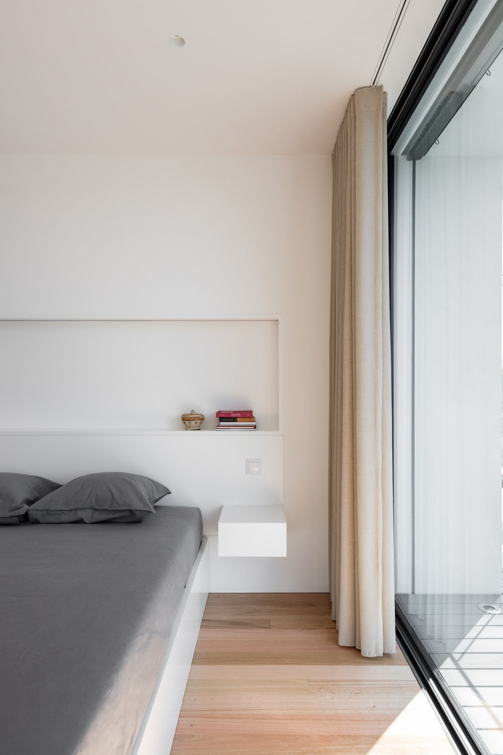 This is a close look at the bedroom that has a built-in platform bed and bedside table along with a large alcove shelf above it.