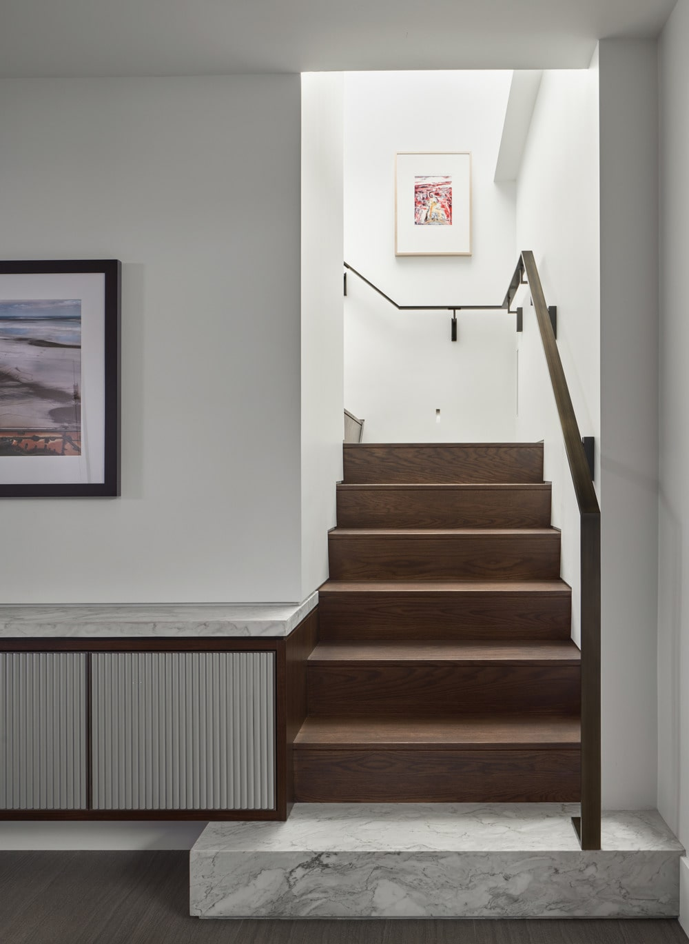 This is a look at the staircase of the house that has wooden steps that match the wooden handrails.