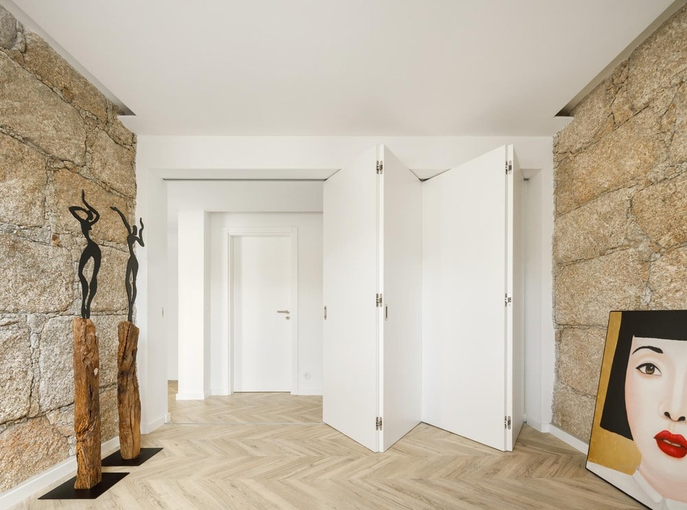 This wall is adorned with a couple of sculptures that stand out against the textured wall.