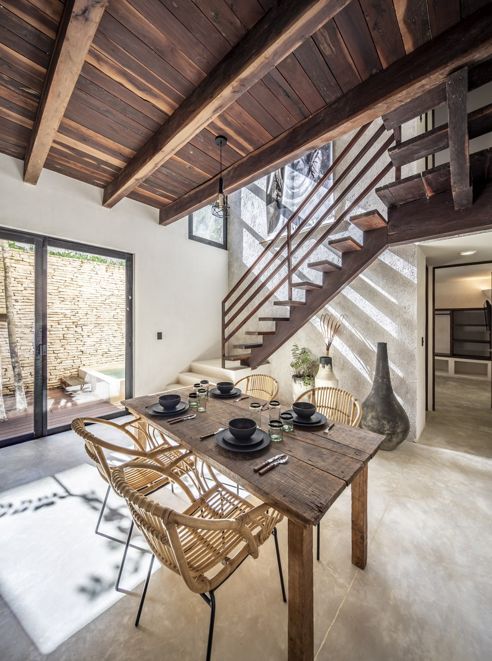 This is a look at the dining area with a wooden rectangular dining table surrounded by woven wicker chairs.