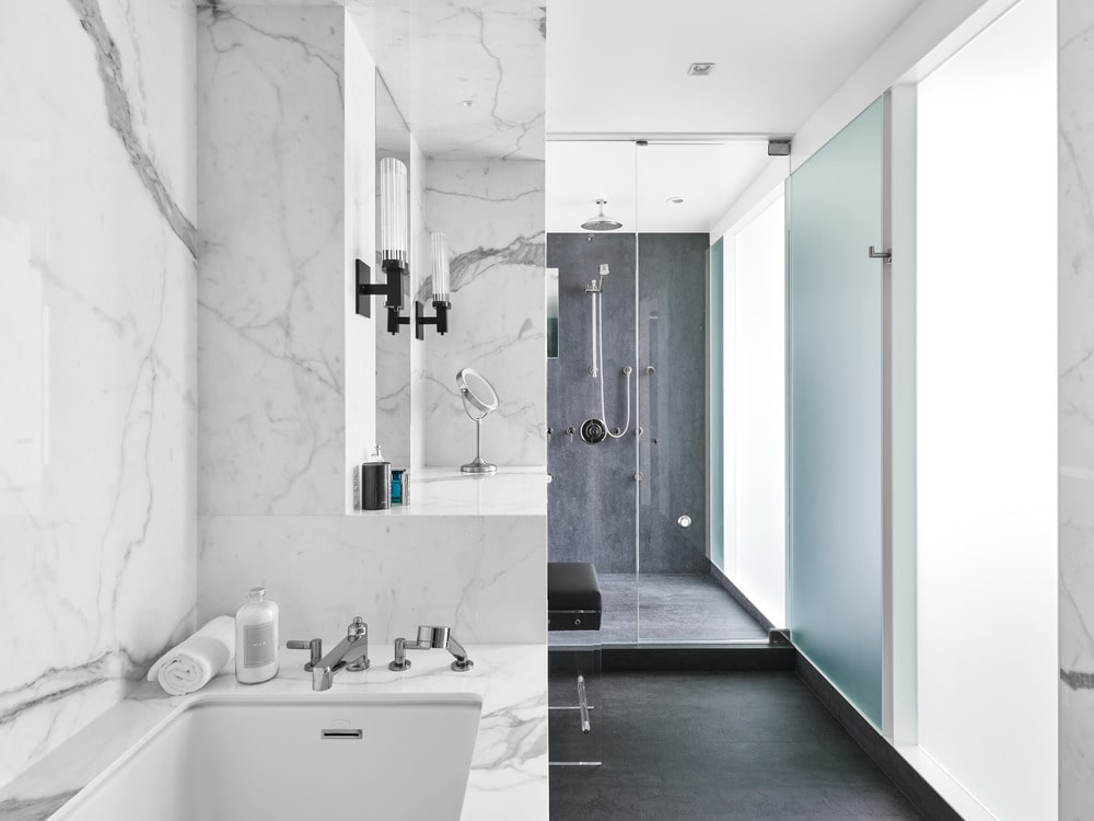 The bathroom has a large shower area on the far wall seen from the vantage of the vanity.