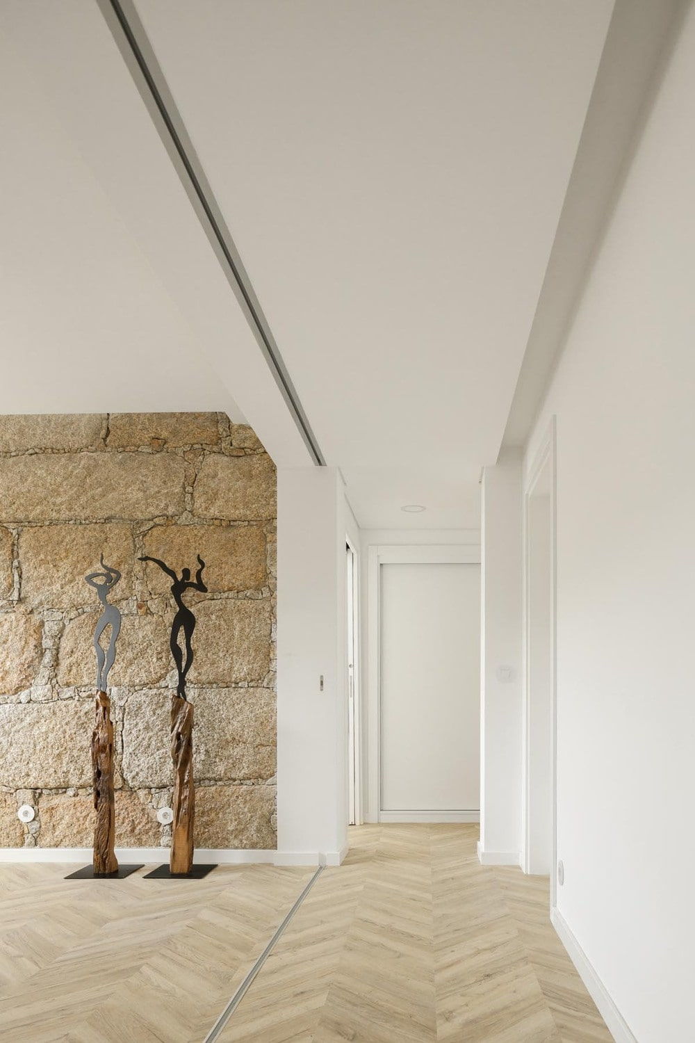 On the other side is another textured stone beige wall that complements the bright white ceiling and folding doors.