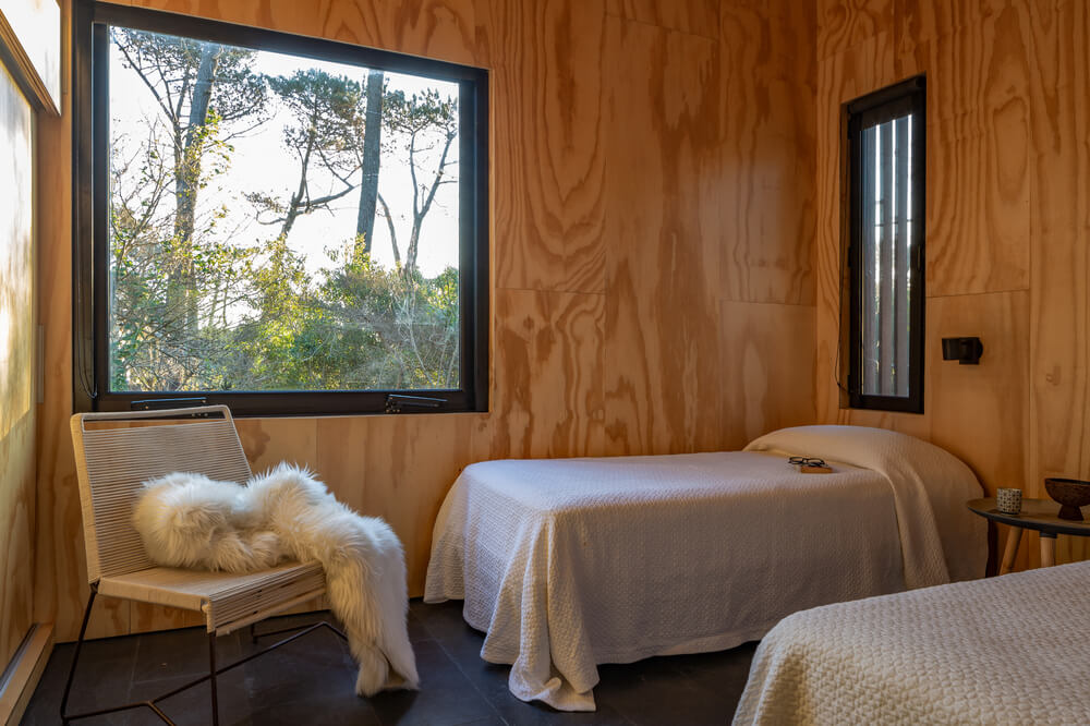 This other bedroom has two small beds and multiple windows that brighten the wooden walls and ceiling.