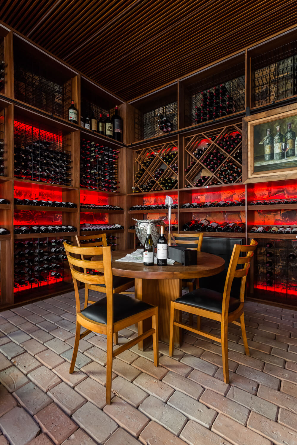The wine cellar has a wooden dining set for a tasting area surrounded by built-in racks of wines.