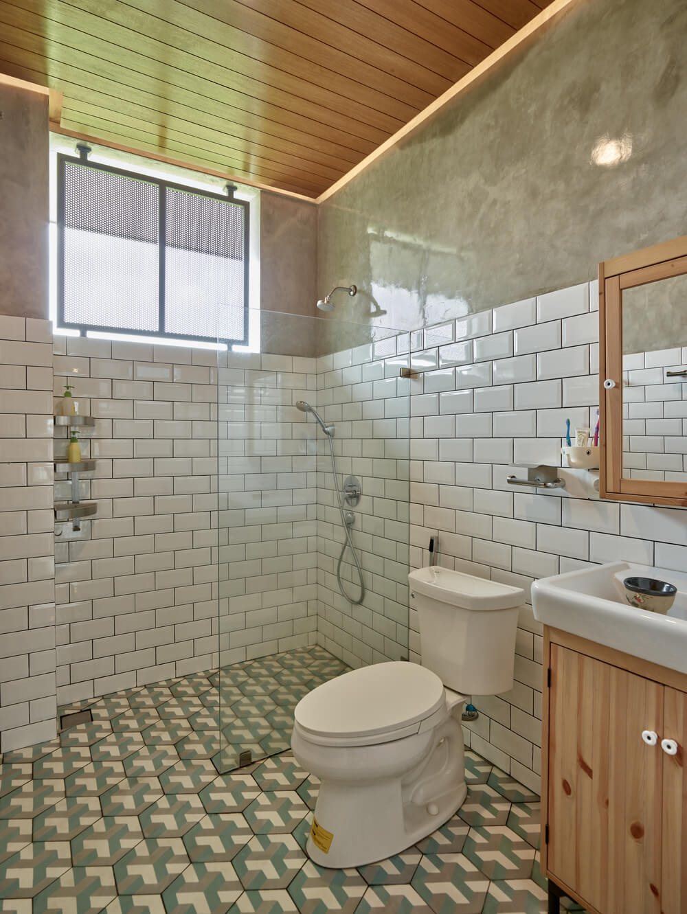 The bathroom has white subway tiles on its walls paired with patterned tiles on the floor that make the toilet and vanity stand out.