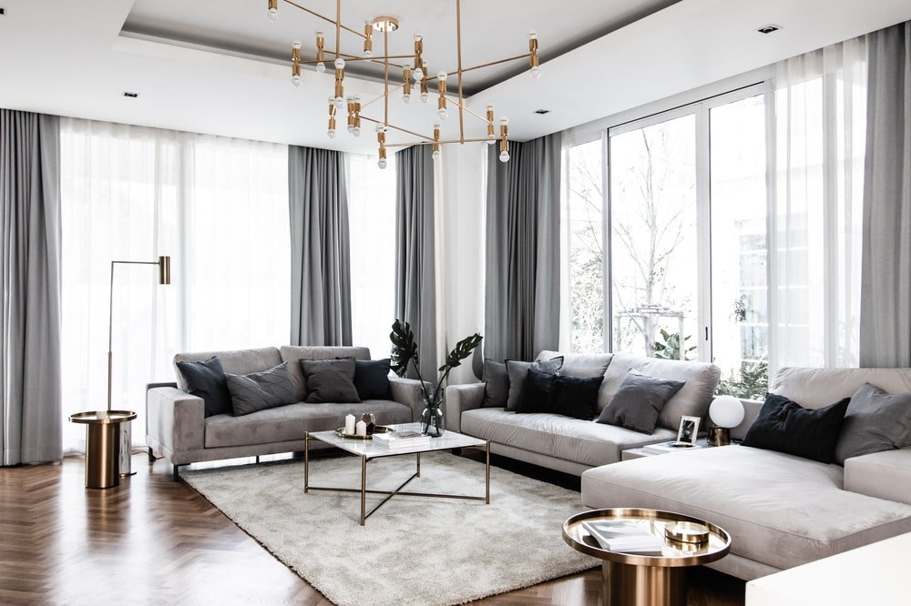 The tray ceiling of the family room has a set of golden decorative chandelier hanging over the coffee table.