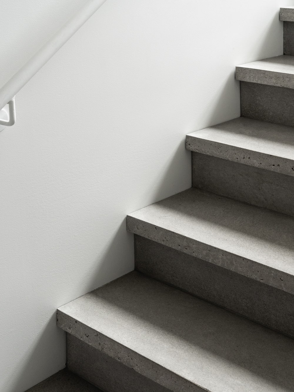 This is a closer look at the concrete steps of the stairs contrasted by the bright walls.