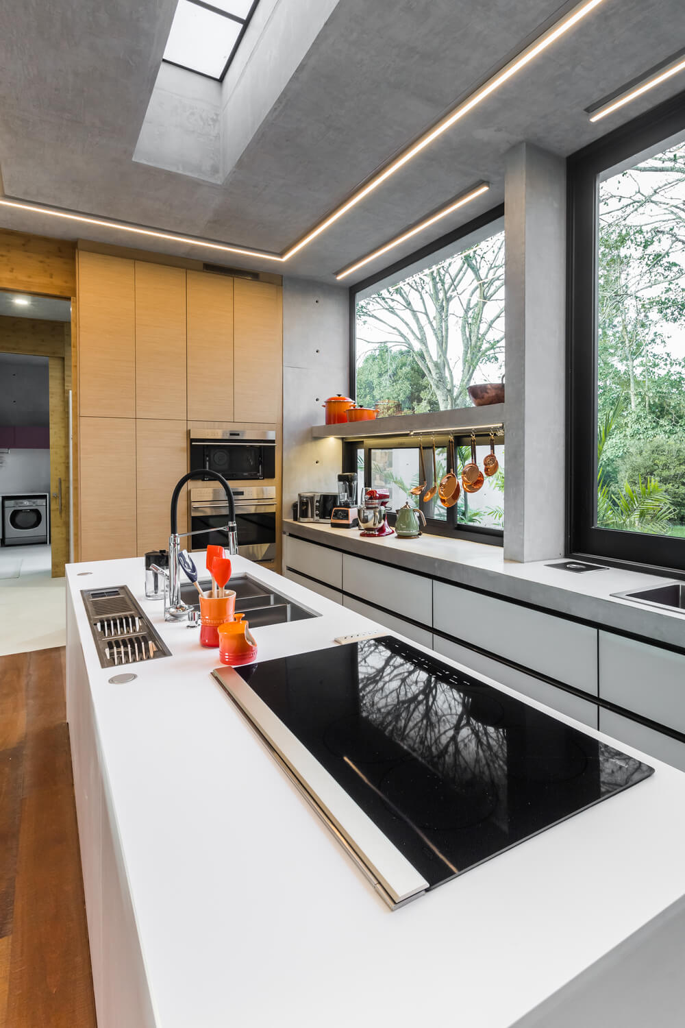 This is a look at the bright and airy kitchen that has lots of natural lighting from the glass windows.