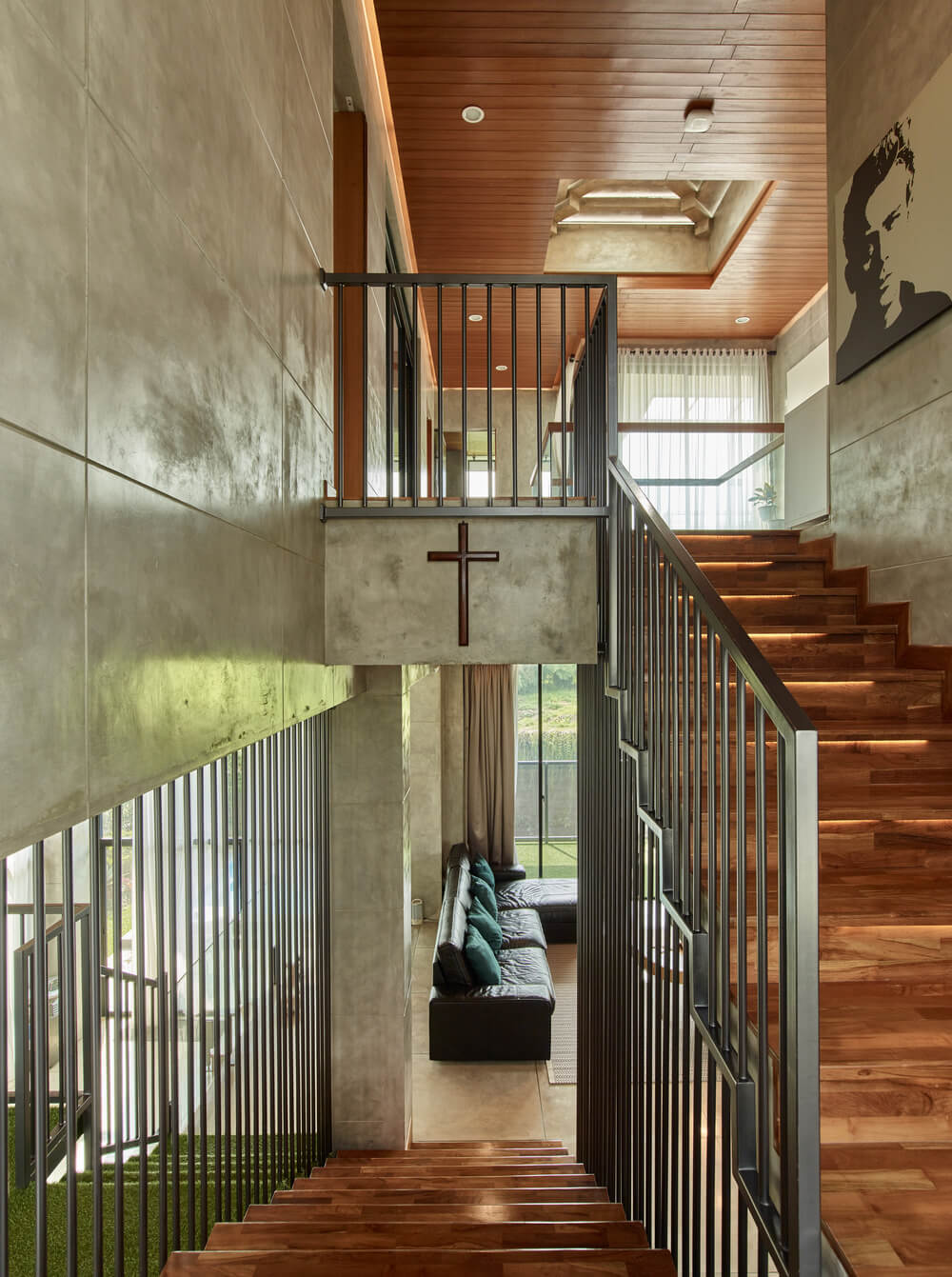 The staircase has wooden steps that stand out against the black railings and concrete walls.