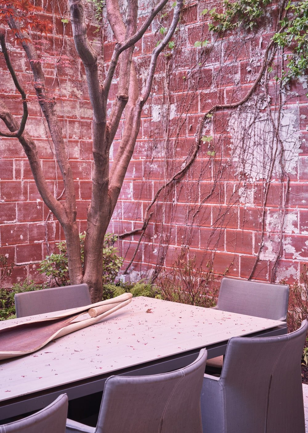 This small outdoor area is adorned by the red brick walls.