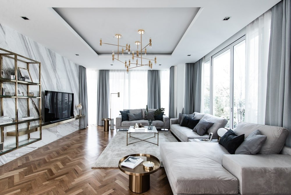 This is the spacious family room with a herring bone hardwood flooring topped with a large tray ceiling.