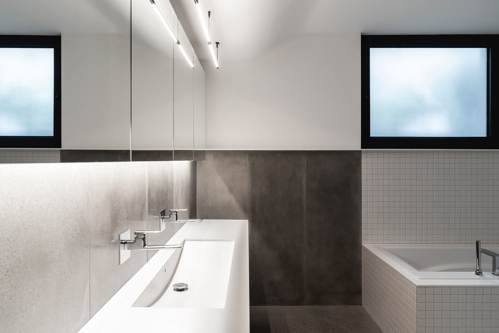 This other bathroom has dark tiles on its lower half of the walls contrasted by the white sink, walls and bathtub.