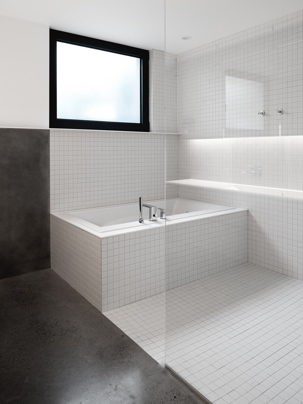 The bathtub is inside a glass-enclosed wet area.