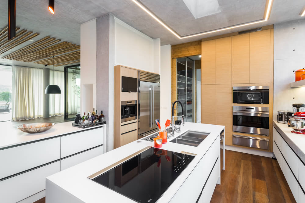 The white modern cabinetry and kitchen island are then complemented by the stainless steel and black elements of the appliances.