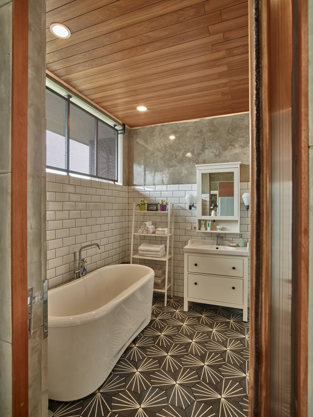 This other bathroom has a large freestanding bathtub under the window paired with white subway tiles on the walls.