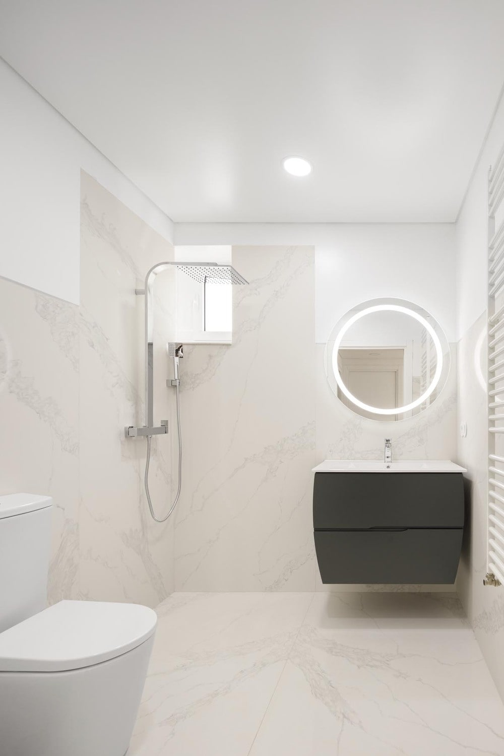 This is a simpler bathroom that has a small floating black vanity that stands out against the surrounding bright beige tones.