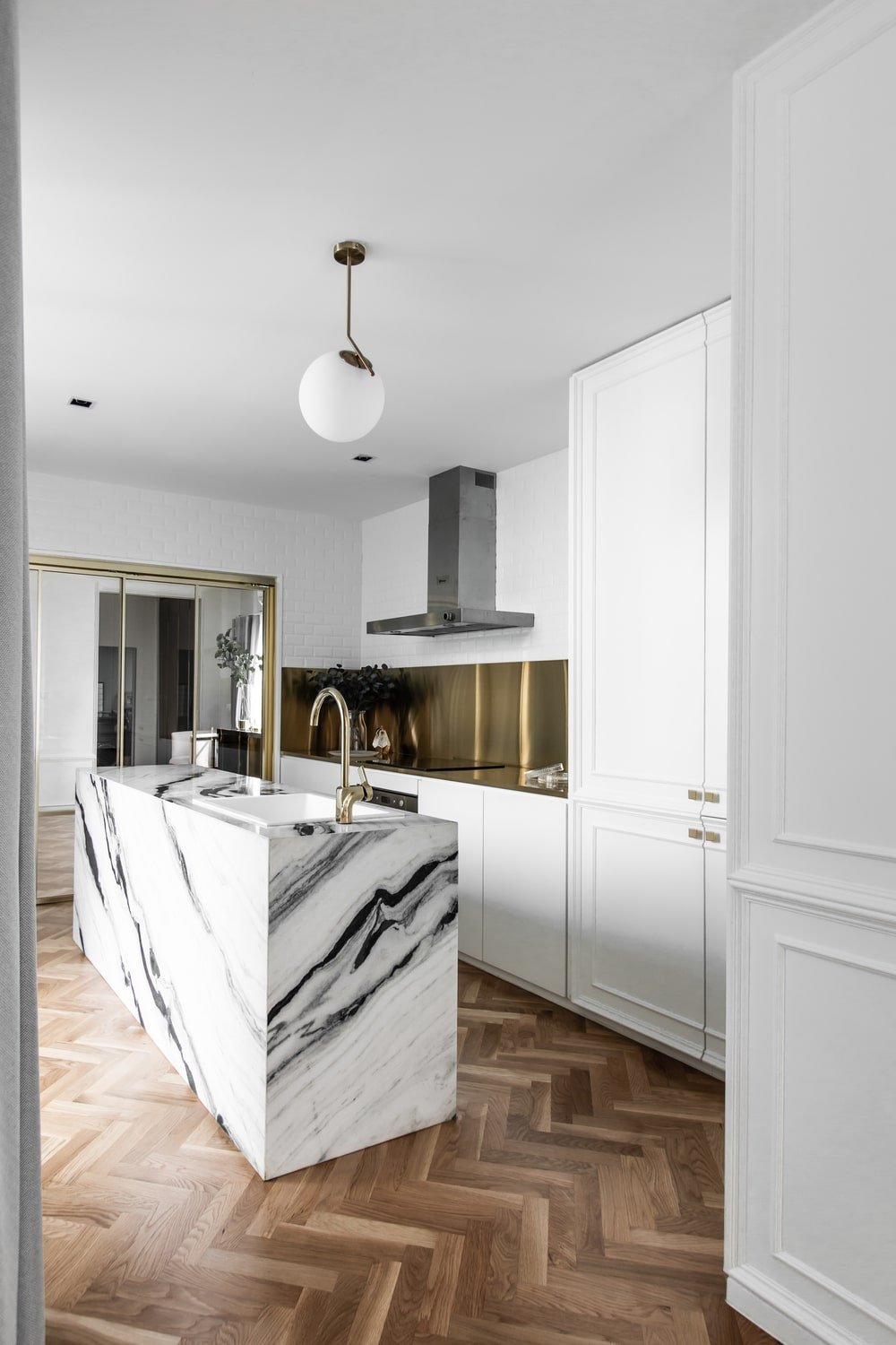 This view showcases the kitchen and its bright white structures contrasted by the herringbone hardwood flooring.