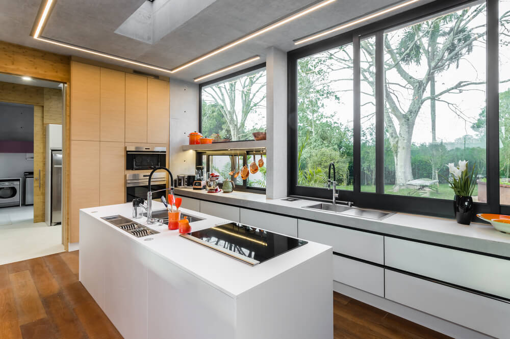 This view also shows that the kitchen has a wooden wall on the far side that pairs well with the darker hardwood flooring.