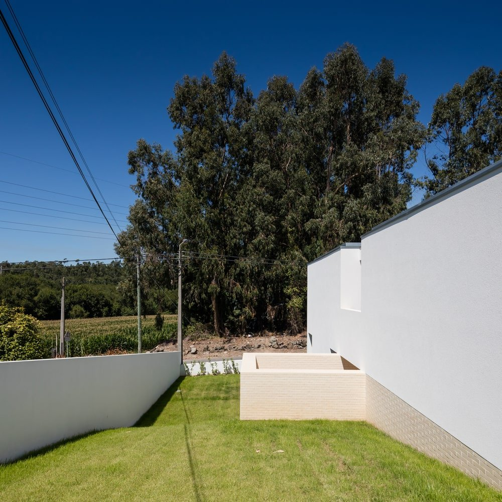 This is a side of the house that has a large grass lawn that complements the neutral textured exterior walls.
