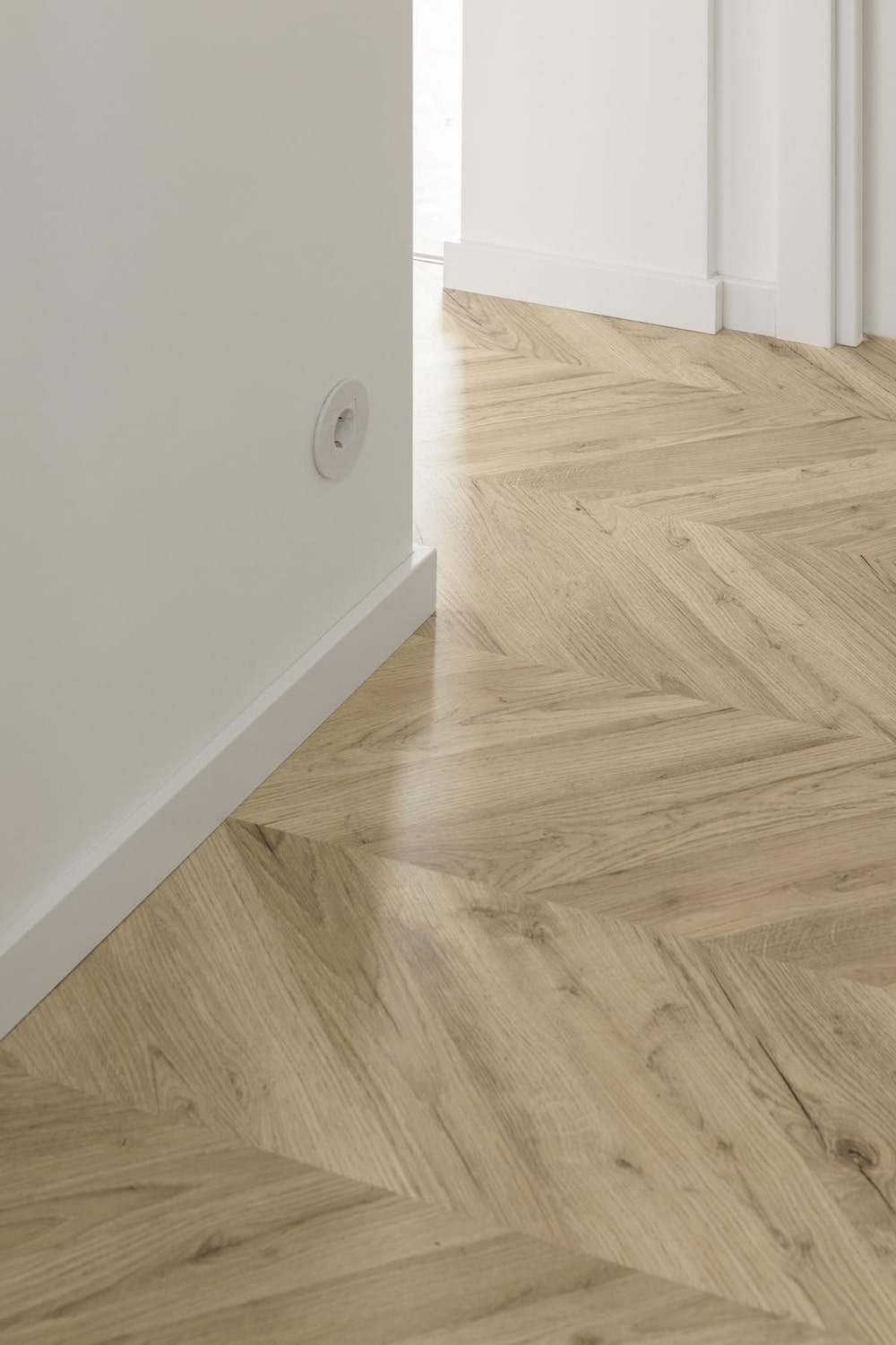 This is a close look at the white wall and how it is complemented by the herringbone marble flooring.