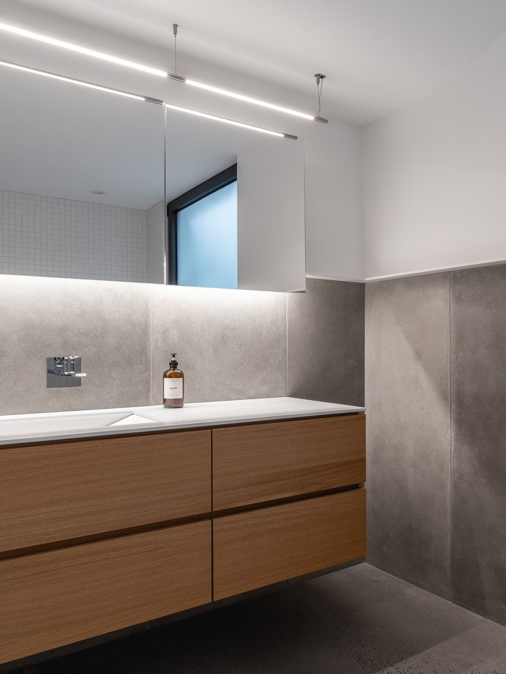 The vanity of the bathroom has bright walls and modern lighting.