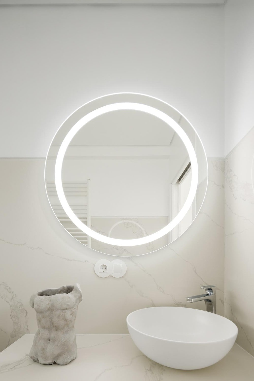 This is a close look at the round wall-mounted vanity mirror with its own lighting.