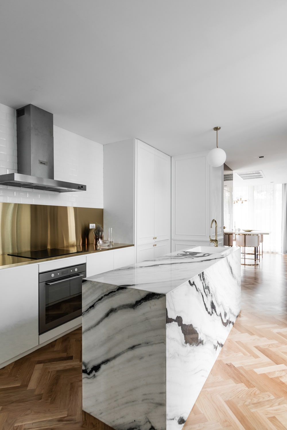 Across the kitche island is the cooking area that has a golden backsplash and a stainless steel vent hood.