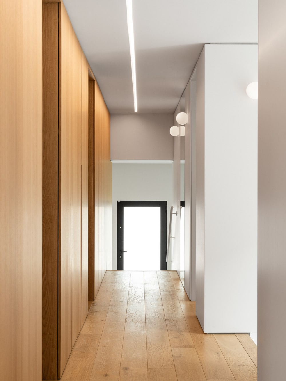 This is a hallway within the house that has wooden walls on the sides brightened by the bright ceiling and pillars.