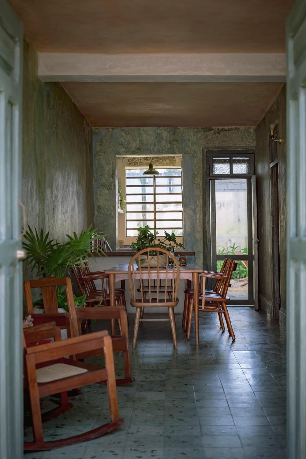 This is a close look at the dining area that has a small wooden dining set that stands out against the green patterned walls.