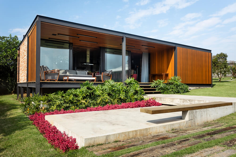 The sides of the concrete walkway is adorned with flowering shrubs and a built-in wooden bench.