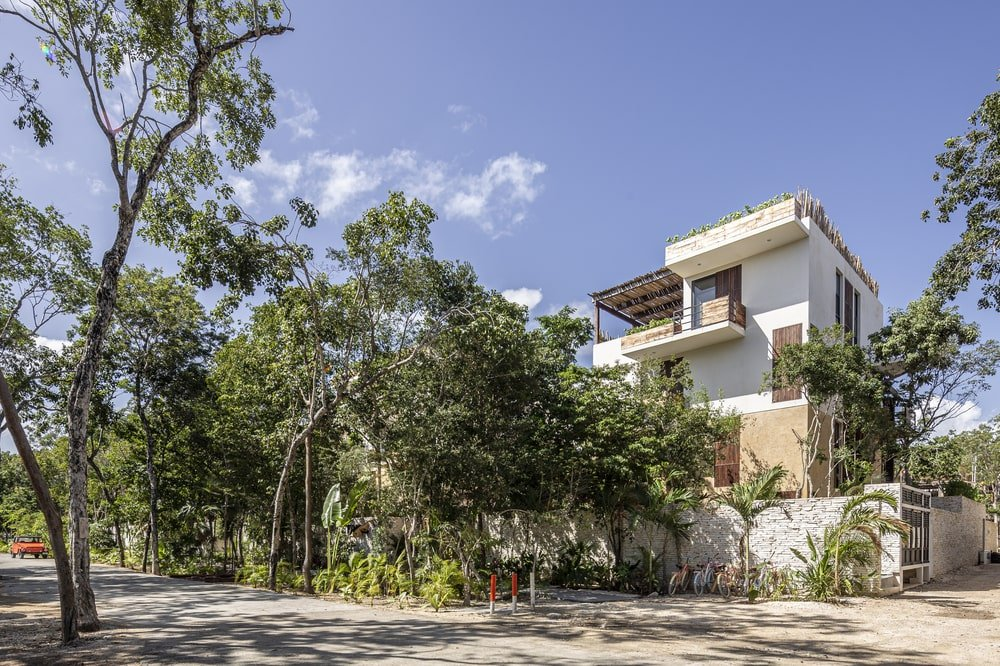 The bright exteriors of the house makes it stand out against the surrounding tall trees of the landscape.
