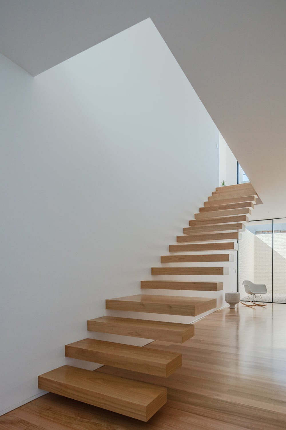 A few steps from the that area is the staircase with a modern floating steps design.