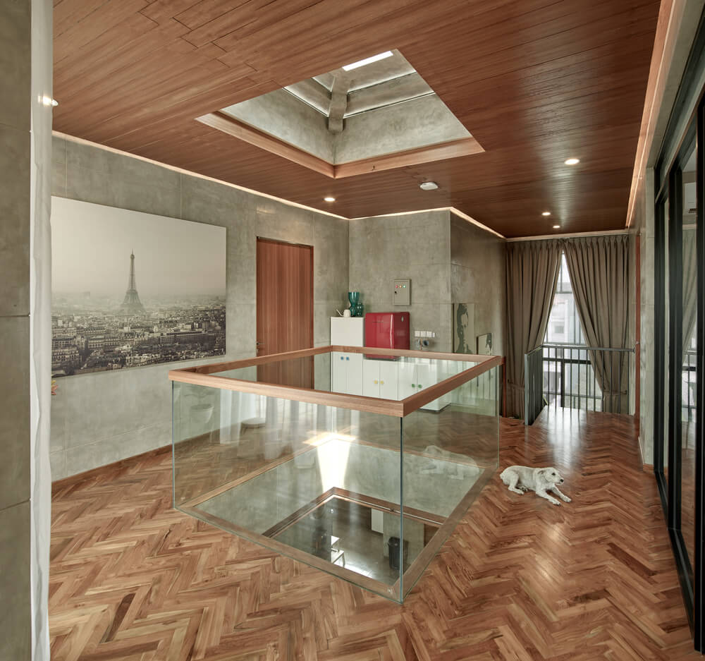 The glass walls of the indoor balcony is surrounded by herringbone hardwood flooring.