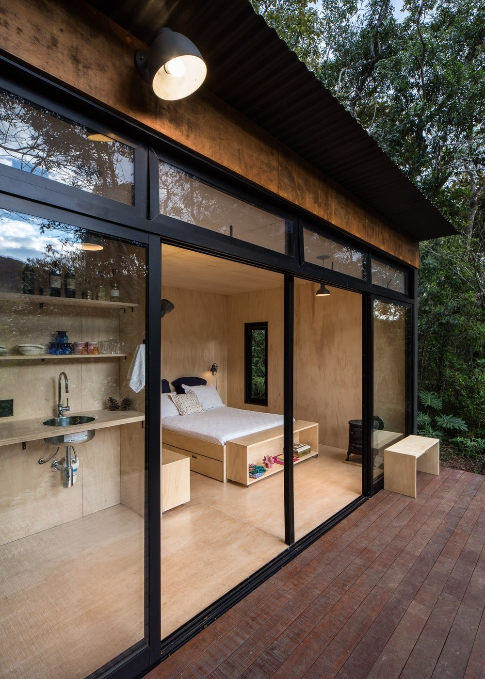 A few steps from the kitchen area is the wooden bed seen from the vantage of the wooden deck terrace.