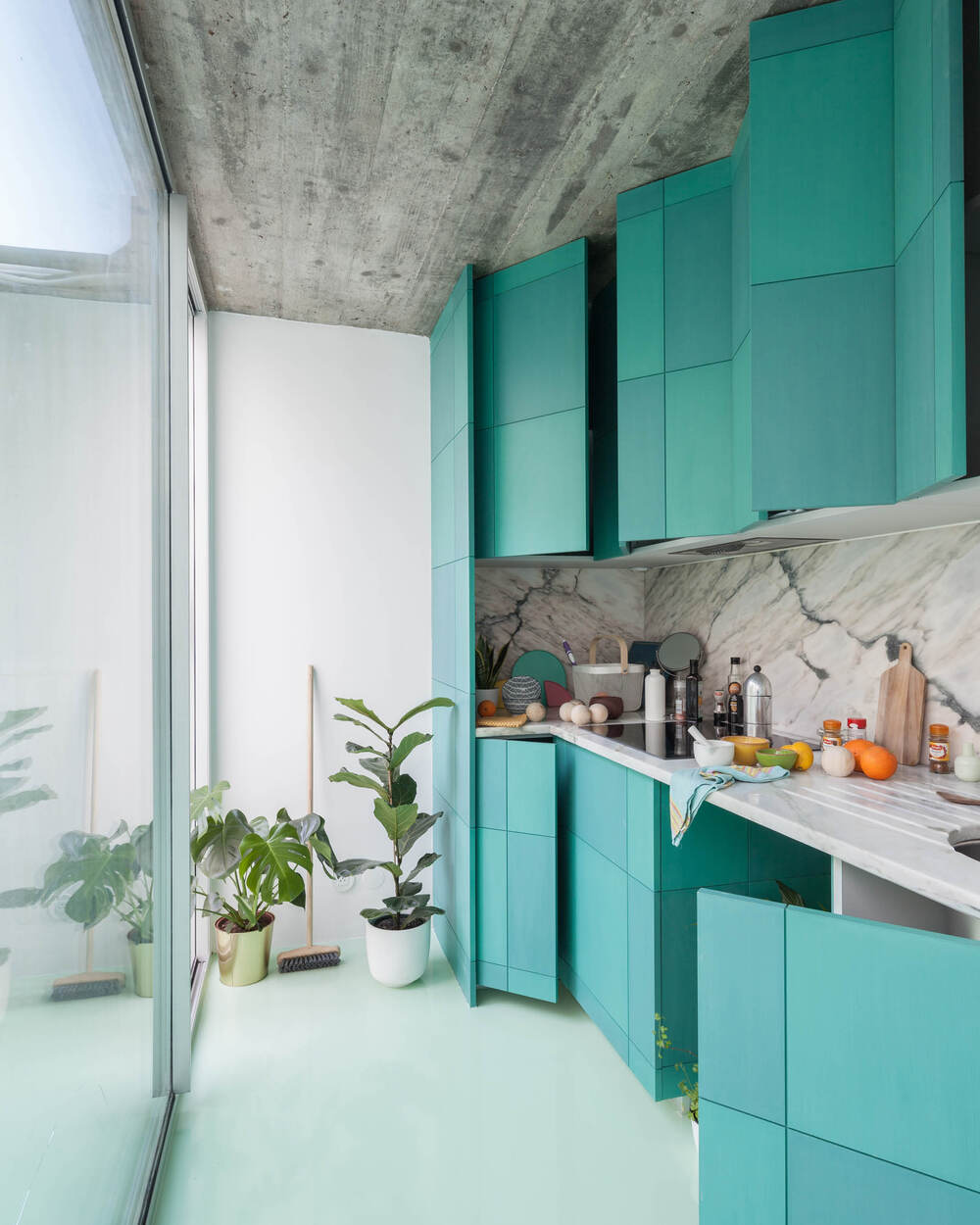 The kitchen has vibrant green cabinetry across from the glass wal.