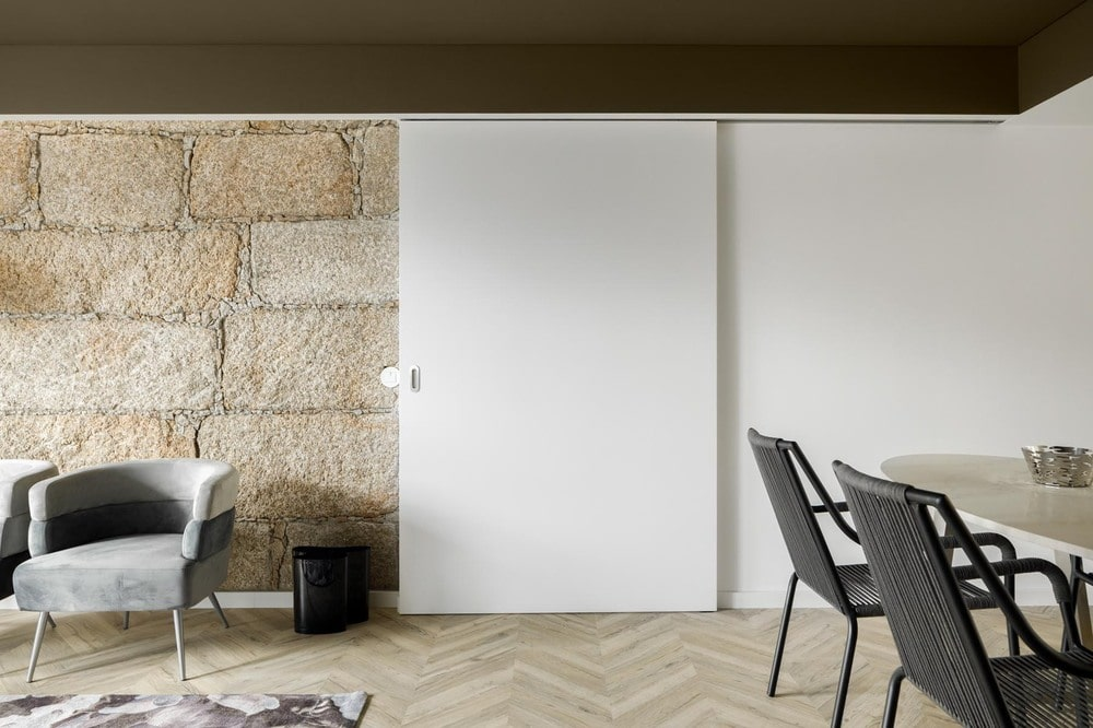 This set of white sliding door si complemented by the large textured stone wall on the side that matches the tone of the herringbone floor.