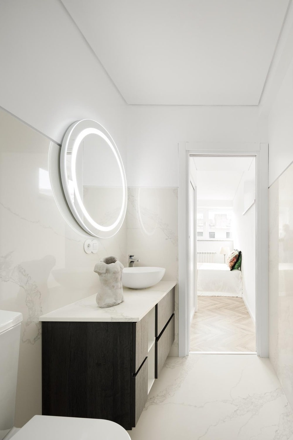 This is the bright white bathroom that is contrasted by the black vanity topped with a circular mirror with lighting.