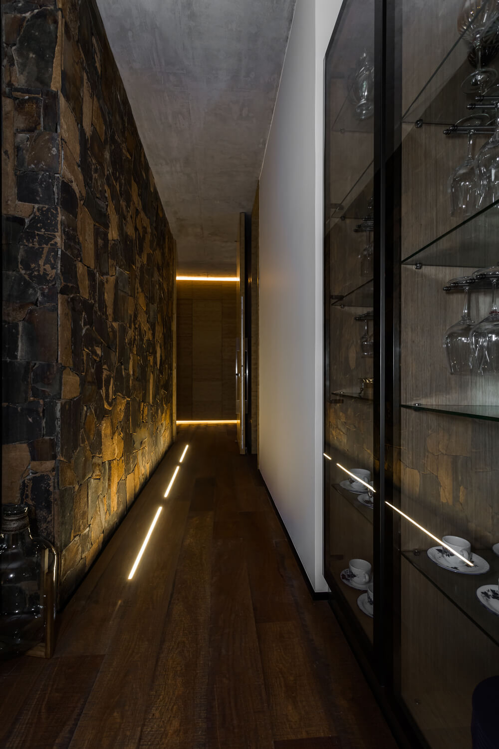 This hallway has a built-in glass-enclosed china cabinet and a large mosaic stone wall.