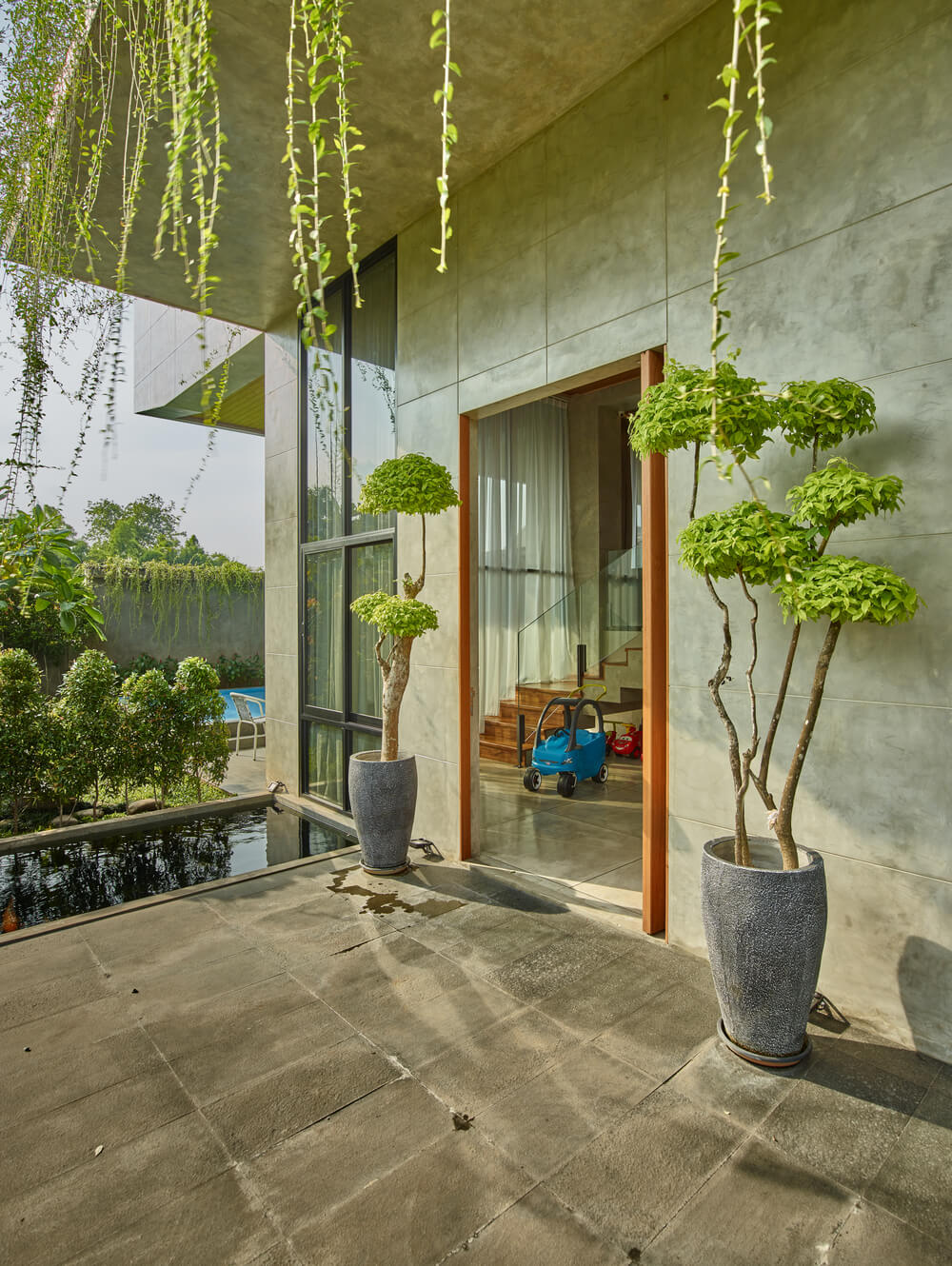 This is the main entrance of the house with a couple of potted plants flanking the main door and small fish pond on the side.