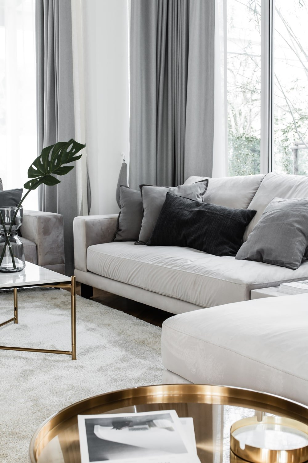 The light beige sofas are adorned with dark gray and gray throw pillows that bring contrast to the sofa.