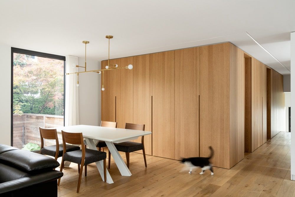 Next to the dining table is the large wooden paneled wall that matches the floor.